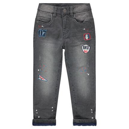 Jeans effet used doublé micropolaire avec taches de peinture et badges