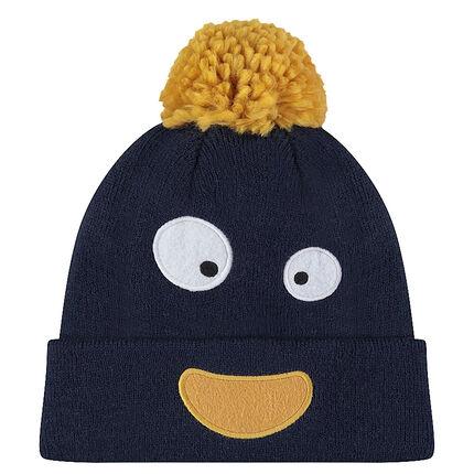 Bonnet en tricot avec pompon jaune et yeux patchés