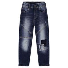 Jeans effet used fourche basse avec patchs et découpes